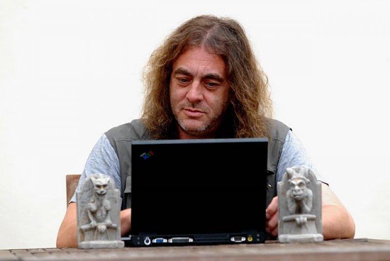 Dennis Price at his desk with ever present gargoyles.